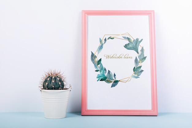 Розовый каркас макета с декоративным кактусом