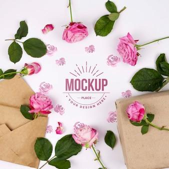封筒の横にあるモックアップをフレーミングするピンクのバラ