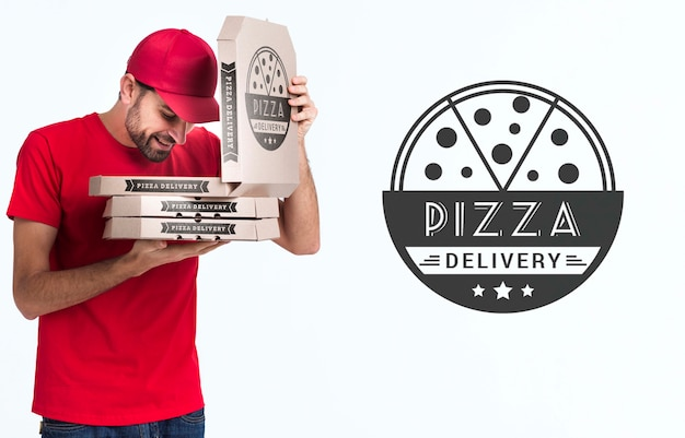 Мальчик-пицца держит коробки и смотрит в одну из них