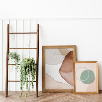Plants hanging on a wooden ladder by picture frame mockups