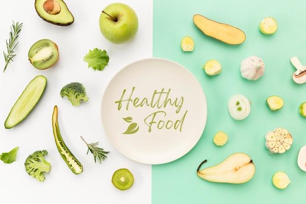 Тарелка в окружении овощей и фруктов плоской планировки