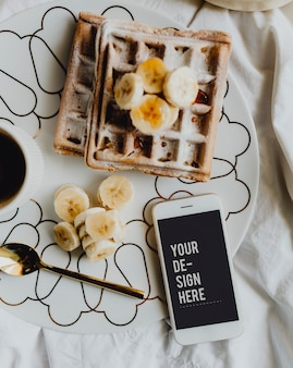Plate of waffle with slices of banana and a cup of coffee next to a smartphone