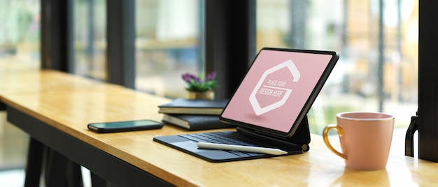 Portable workspace with mockup digital tablet, supplies and coffee mug