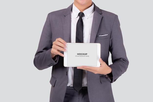 Портрет бизнесмена показывая и представляя планшетный экран макета