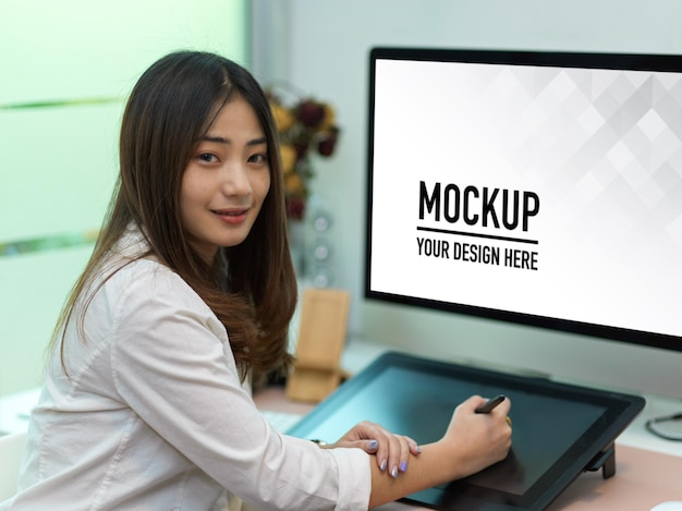 Portrait of female office worker working with drawing tablet and computer mockup
