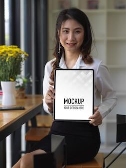 Portrait of female student showing tablet mockup