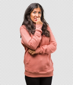 Portrait of fitness young indian woman biting nails, nervous and very anxious and scared for the future, feels panic and stress