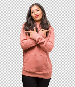 Portrait of fitness young indian woman confused and doubtful, decide between two options, concept of indecision
