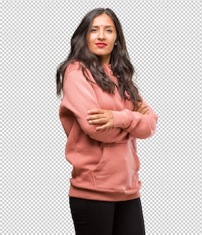 Portrait of fitness young indian woman crossing his arms, smiling and happy
