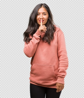 Portrait of fitness young indian woman keeping a secret or asking for silence, serious face, obedience concept