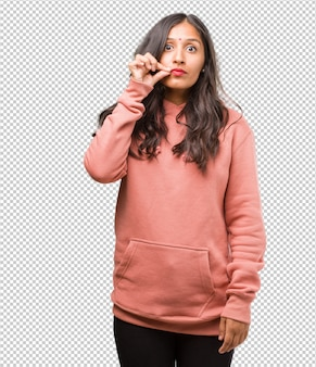 Portrait of fitness young indian woman keeping a secret or asking for silence