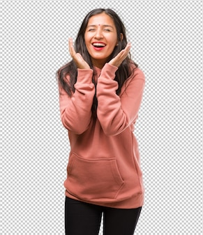 Portrait of fitness young indian woman laughing and having fun, being relaxed and cheerful, feels confident and successful