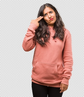 Portrait of fitness young indian woman making a suicide gesture, feeling sad and scared forming a gun with fingers
