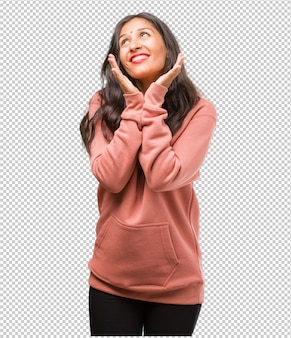 Portrait of fitness young indian woman surprised and shocked, looking with wide eyes, excited by an offer or by a new job, win concept