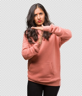 Portrait of fitness young indian woman tired and bored, making a timeout gesture, needs to stop because of work stress, time concept