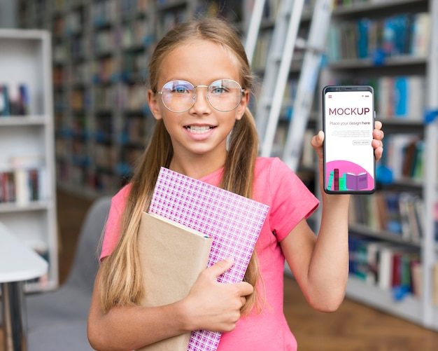Portrait of girl in library showing mock-up phone
