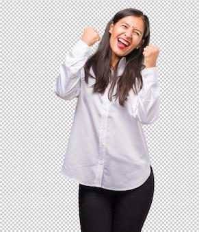 젊은 인도 여자의 초상화 매우 행복하고 흥분, 팔을 제기, 승리 또는 성공을 축하, 복권 당첨