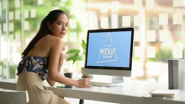 Портрет модельера женского пола смотрит в камеру и улыбается во время работы за компьютерным столом