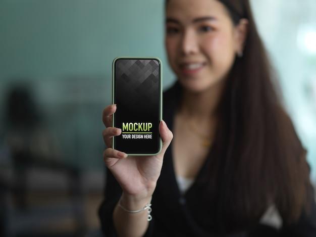 Портрет женщины в черном костюме, держащей смартфон, чтобы показать макет экрана