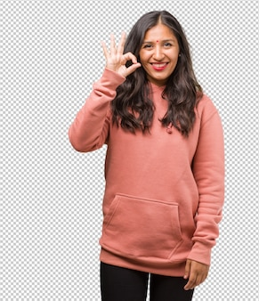 Портрет молодой индийской женщины фитнеса жизнерадостной и уверенно делающей одобренный жест, взволнованный и кричащий, концепция одобрения и успеха