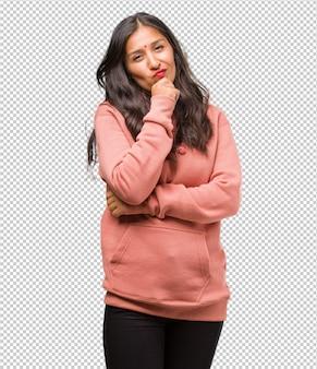 考えて見上げて、アイデアについて混乱しているフィットネス若いインド人女性の肖像画は、解決策を見つけようとしている