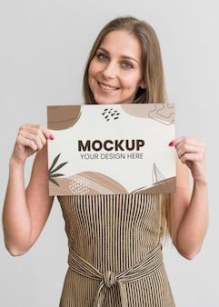 モックアップ紙を保持している女性の肖像画