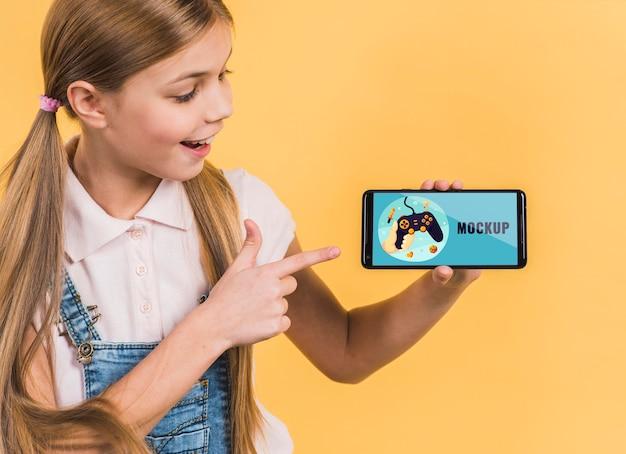Портрет молодой девушки, держащей мобильный телефон