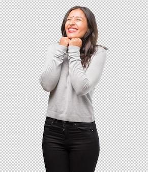 Портрет молодой индийской женщины очень рад и взволнован, поднимая руки, празднуя победу или успех, выигрывая в лотерею