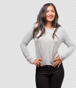 Портрет молодой индийской женщины с руки на бедрах, стоя, расслабленный и улыбающийся, очень позитивный и веселый