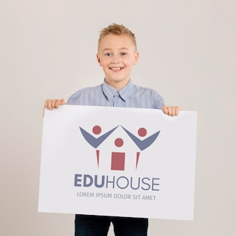 Portrait of young boy holding mock-up sign