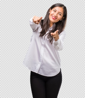 Portrait of a young indian woman cheerful and smiling pointing to the front