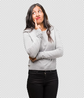 Portrait of young indian woman doubting and confused, thinking of an idea or worried about something