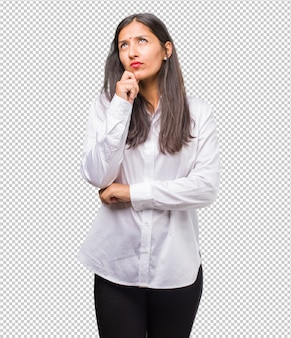 Portrait of a young indian woman doubting and confused, thinking of an idea or worried about something