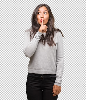 Portrait of young indian woman keeping a secret or asking for silence, serious face