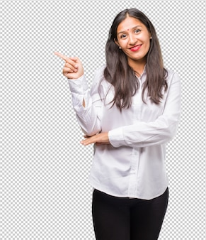 Portrait of a young indian woman pointing to the side, smiling surprised presenting something