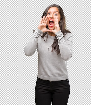 Portrait of young indian woman screaming happy, surprised by an offer or a promotion, gaping, jumping and proud