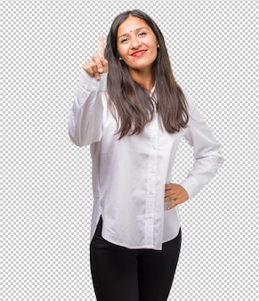 Portrait of a young indian woman showing number one, symbol of counting,  mathematics, confident and cheerful