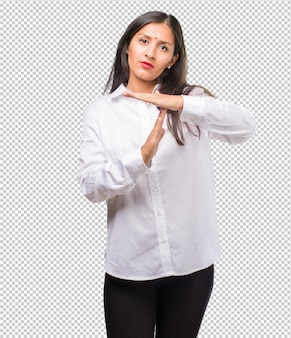 Portrait of a young indian woman tired and bored, making a timeout gesture, needs to stop because of work stress, time
