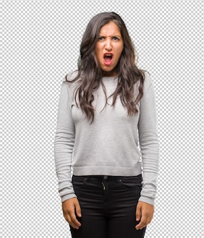Portrait of young indian woman very angry and upset, very tense, screaming furious, negative and crazy