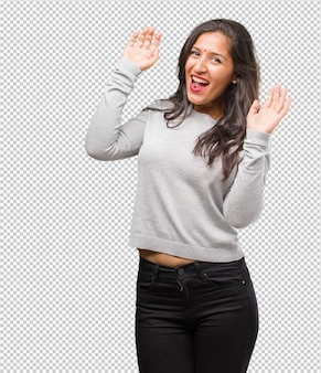 Portrait of young indian woman very happy and excited, raising arms, celebrating a victory or success, winning the lottery
