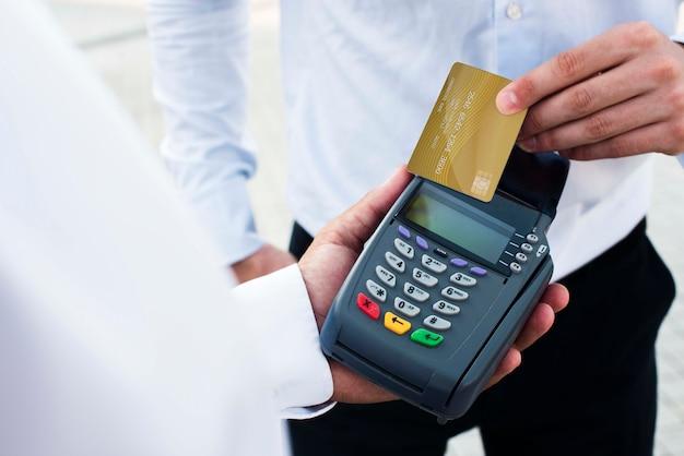 Pos терминал и кредитная карта с бизнесменами на открытом воздухе