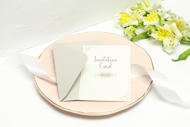 Postcard on pink plate with white ribbon, grey envelope and white flowers