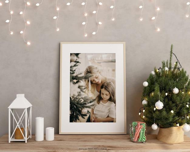 3d 렌더링에서 크리스마스 트리가 있는 테이블에 있는 포스터 프레임 모형