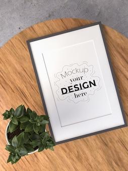 Макет рамки плаката на деревянном столе