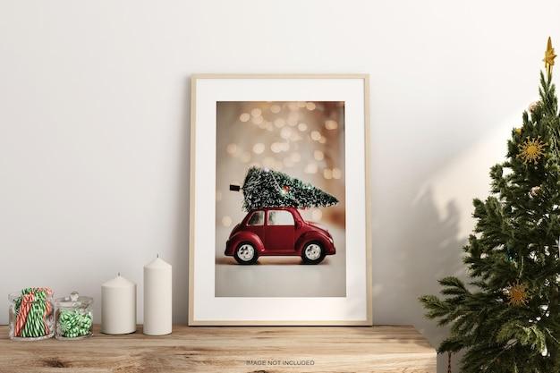 Woden 테이블에 크리스마스 트리와 포스터 프레임 모형