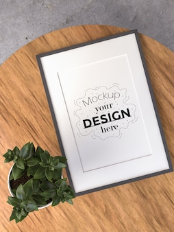 Poster frame mockup on wooden table