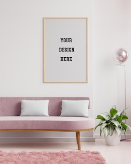 Poster mockup with vertical frame on empty white wall in living room interior with pink velvet sofa
