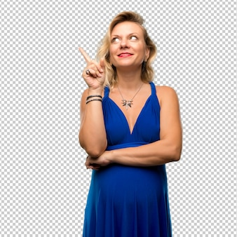 Pregnant blonde woman with blue dress pointing with the index finger a great idea