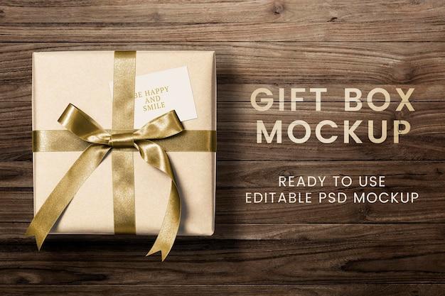 Presentare il tag di auguri mockup psd su una confezione regalo con testo be happy and smile