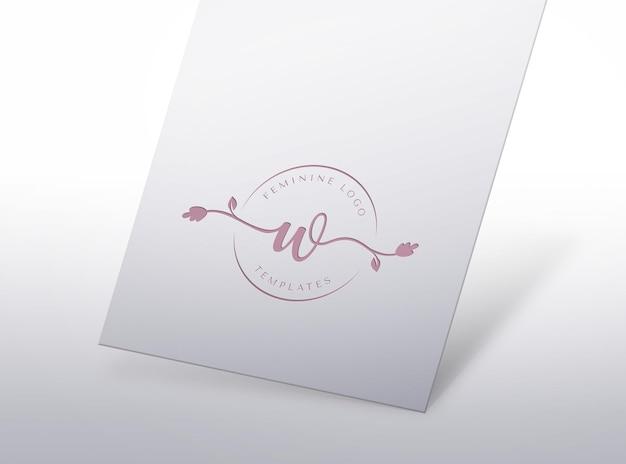 白い紙にプレスされたフェミニンなロゴのモックアップ